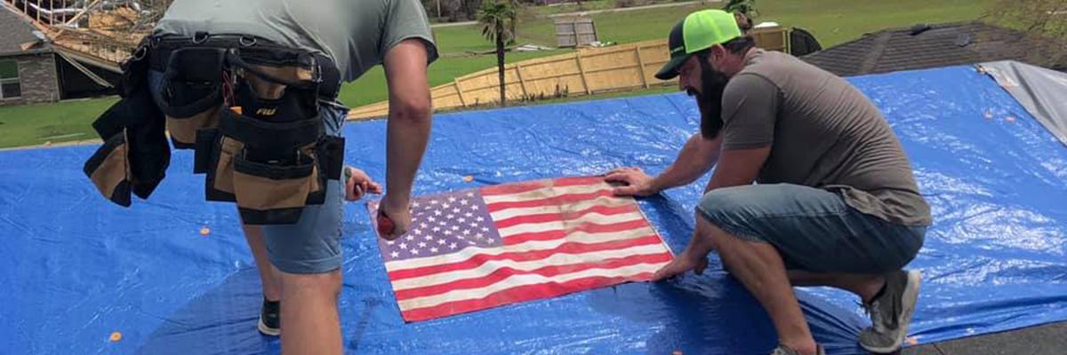 Men put tarp on house after Hurricane Laura devestates Lake Charles, Louisiana
