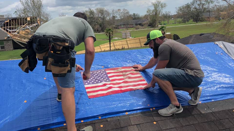 Men put tarp on house after Hurricane Laura devestates Lake Charles, Louisiana